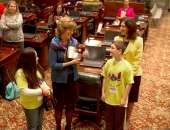 Fifth graders Devynne Valentin and Broderic Shipe present a plaque to Sen. Judy Schwank.